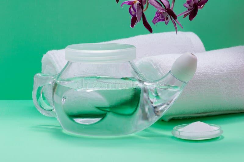 Potenciômetro com ponta macia do conforto, pilha de Neti de flores salinas, roxas da orquídea e rolado acima das toalhas brancas  fotos de stock royalty free