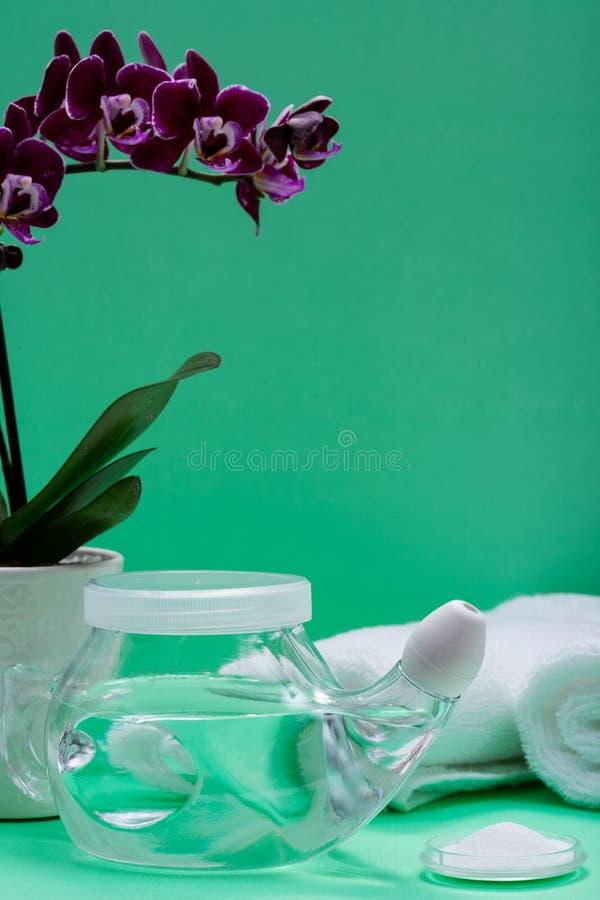 Potenciômetro com ponta macia do conforto, pilha de Neti de flores salinas, roxas da orquídea e rolado acima das toalhas brancas  fotografia de stock royalty free