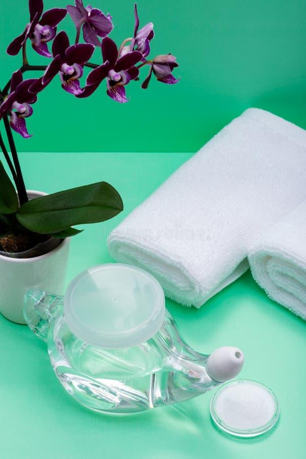 Potenciômetro com ponta macia do conforto, pilha de Neti de flores salinas, roxas da orquídea e rolado acima das toalhas brancas  imagens de stock royalty free