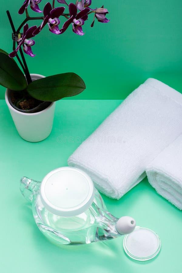 Potenciômetro com ponta macia do conforto, pilha de Neti de flores salinas, roxas da orquídea e rolado acima das toalhas brancas  fotografia de stock