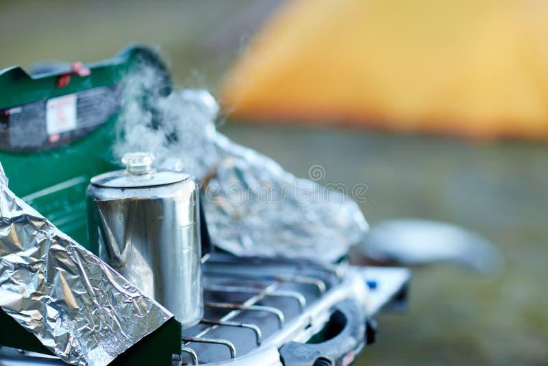 Potenciômetro da água que ferve em um queimador de gás portátil foto de stock
