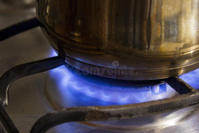 Potenciômetro de aço da caçarola que é caloroso por um fogão foto de stock royalty free