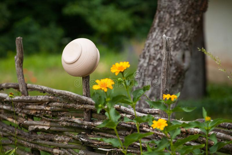 Potenciômetro de argila cerâmico vantajoso que pendura na cerca do salgueiro cercada por y fotografia de stock