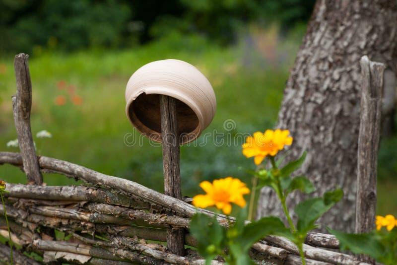 Potenciômetro de argila cerâmico vantajoso que pendura na cerca do salgueiro cercada por y foto de stock royalty free