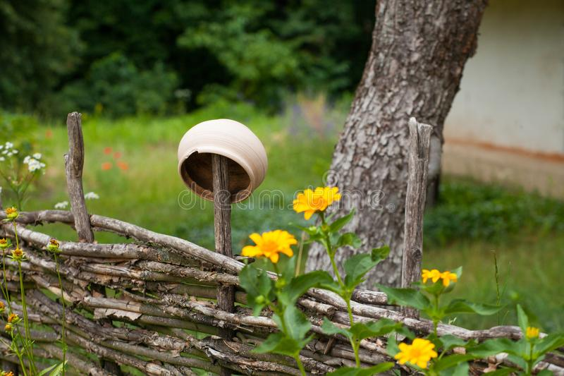 Potenciômetro de argila cerâmico vantajoso que pendura na cerca do salgueiro cercada por y fotografia de stock royalty free