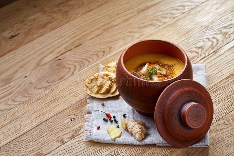Potenciômetro de argila da sopa da abóbora no fundo de madeira rústico do guardanapo homespun, close-up, foco seletivo, vista sup imagens de stock
