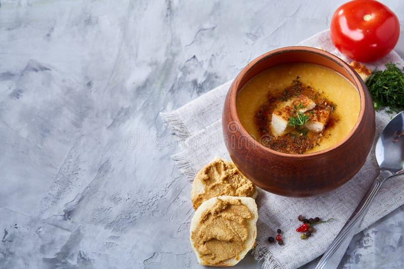 Potenciômetro de argila da sopa da abóbora no guardanapo sobre o fundo textured branco, close-up, foco seletivo, vista superior fotografia de stock