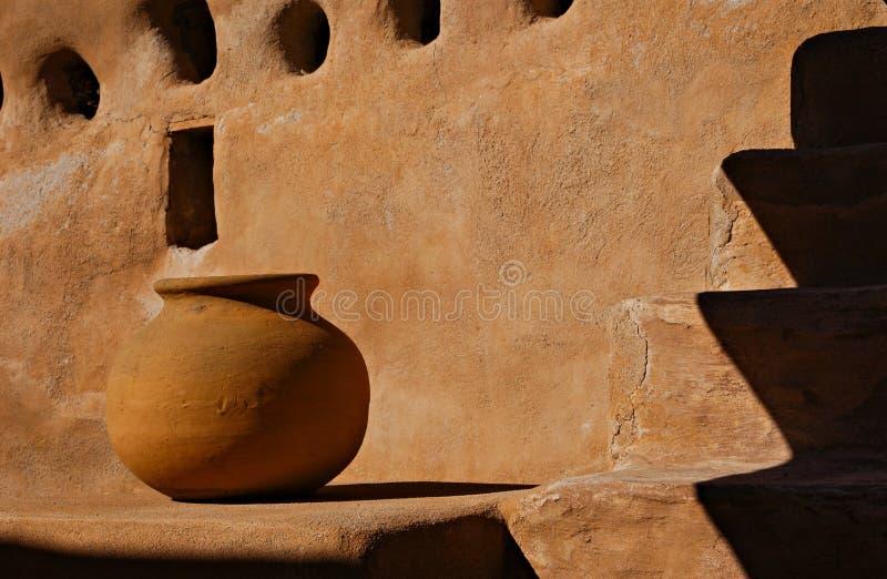 Potenciômetro de argila de encontro à parede de Adobe imagem de stock royalty free