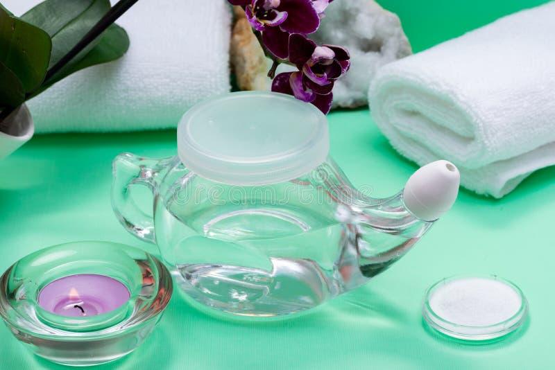 Potenciômetro de Neti, pilha de toalhas brancas salinas, roladas, de flores roxas da orquídea e de vela da luz do chá da alfazema fotografia de stock royalty free