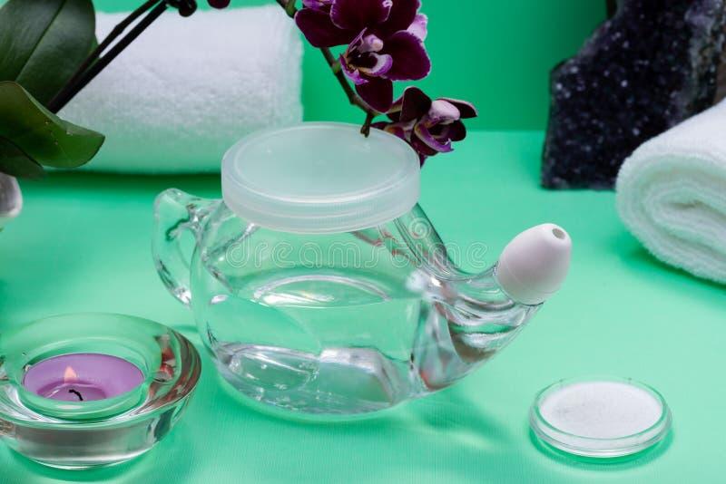 Potenciômetro de Neti, pilha de toalhas brancas salinas, roladas, de flores roxas da orquídea e de vela da luz do chá da alfazema foto de stock royalty free