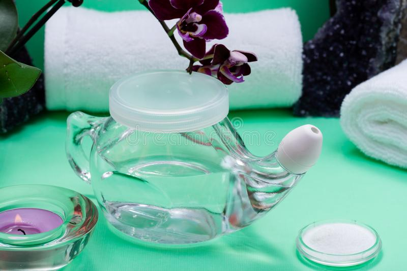Potenciômetro de Neti, pilha de toalhas brancas salinas, roladas, de flores roxas da orquídea e de vela da luz do chá da alfazema imagem de stock royalty free