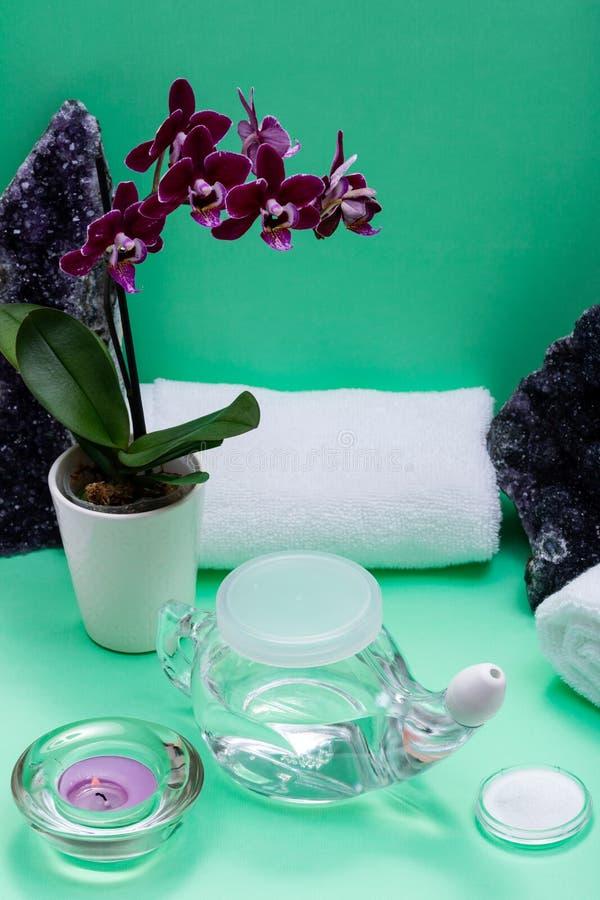 Potenciômetro de Neti, pilha de toalhas brancas salinas, roladas, de flores roxas da orquídea e de vela da luz do chá da alfazema imagem de stock