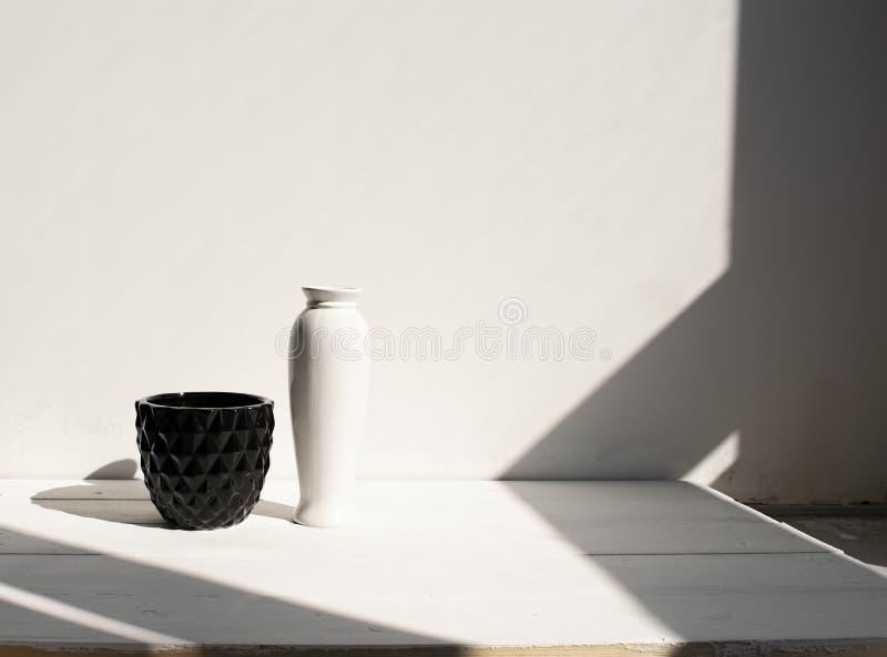 Potenciômetro preto com o vaso branco na tabela de madeira Parede branca, fundo com luz solar e sombras Interior moderno foto de stock