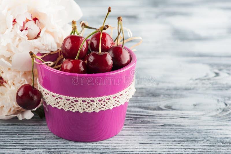 Potenciômetro roxo com cheriies e peônias imagens de stock royalty free