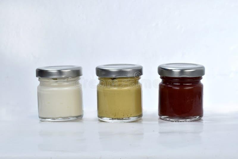 Potenciômetros com mostarda e ketchup da maionese no fundo branco fotos de stock