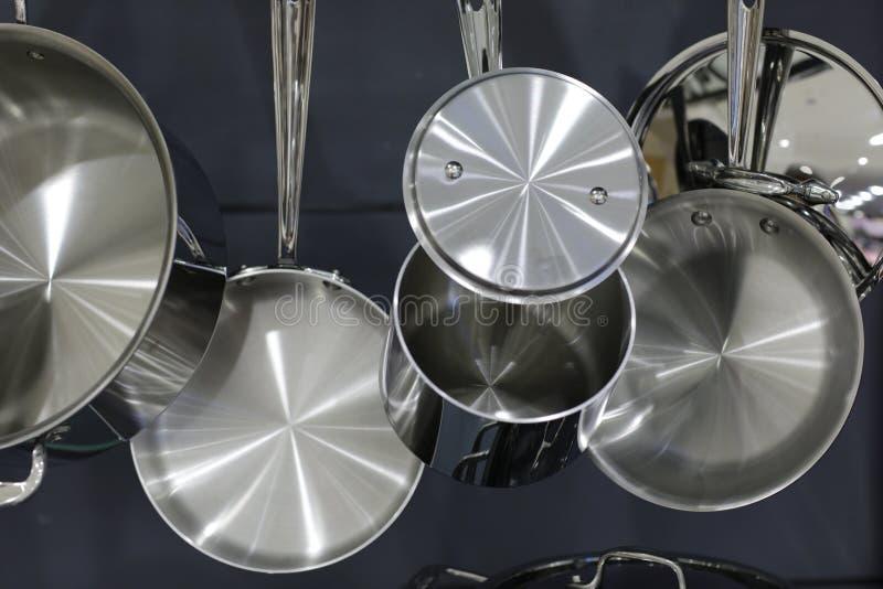 Potenciômetros de aço inoxidável e bandejas que penduram na cozinha foto de stock royalty free
