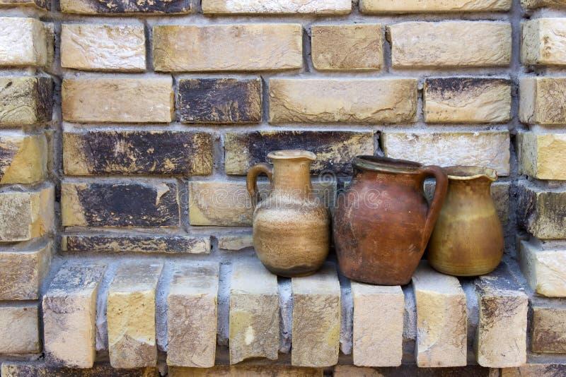 Potenciômetros de argila em uma parede de tijolo imagem de stock