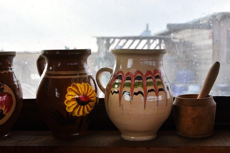 Potenciômetros romenos tradicionais em uma prateleira de madeira em uma casa velha, na frente de uma janela imagens de stock