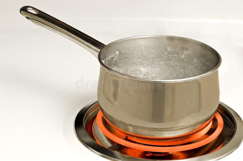 Potenciômetro da água a ferver no queimador quente fotografia de stock