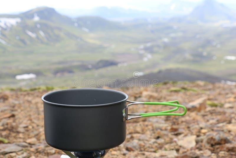 Potenciômetro de acampamento no fogão de gás portátil Passeio na montanha de Landmannalaugar fotografia de stock royalty free