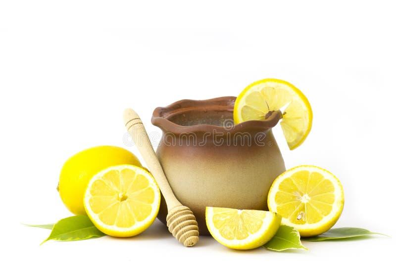 Potenci?metro de argila com mel e os lim?es frescos imagem de stock royalty free