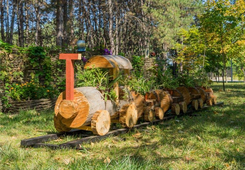 Potenciômetro de flor sob a forma de um trem feito da madeira fotografia de stock