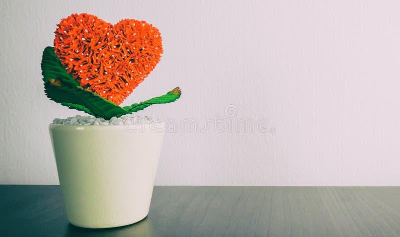 Potenciômetro de flor vermelho do coração na tabela imagem de stock royalty free