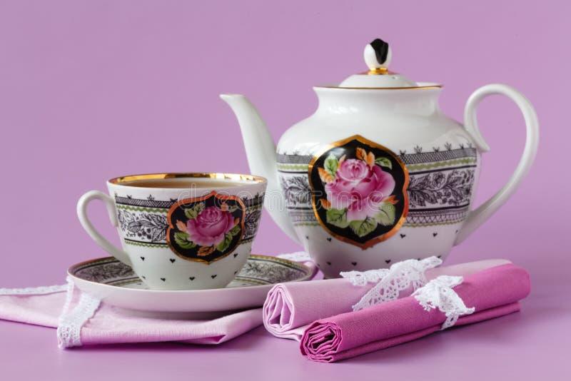 Potenciômetro e copo do chá da porcelana no fundo cor-de-rosa foto de stock