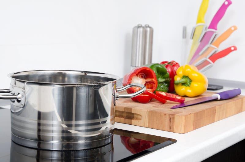 Potenciômetro e vegetais na cozinha moderna com fogão da indução fotografia de stock