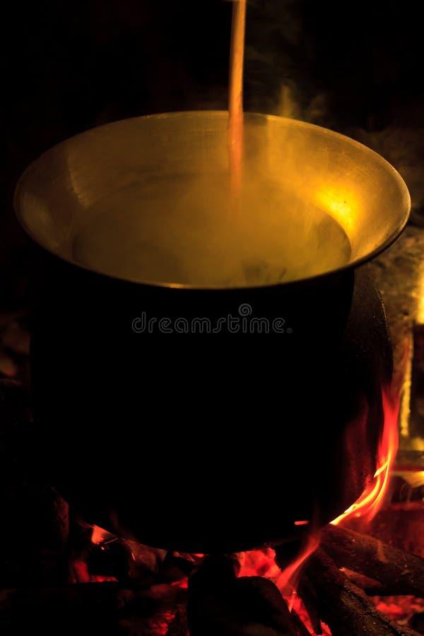 Potenciômetro grande no fogo do acampamento na noite Montanhas da mola fotografia de stock