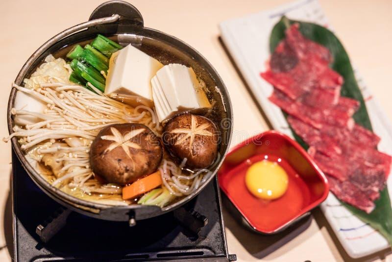 Potenci?metro quente do sukiyaki japon?s com vegetal, fatia da carne, ovo cru imagens de stock