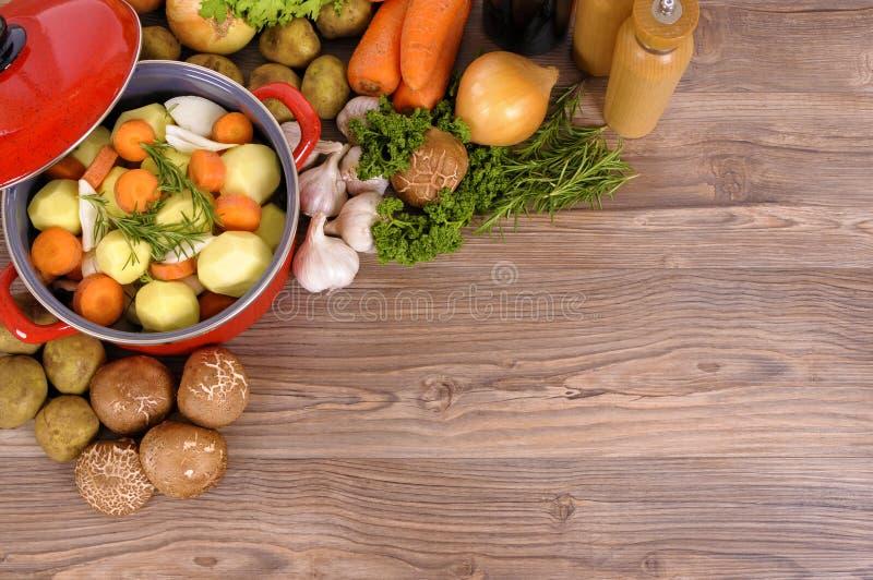 Potenciômetro vegetal com ingredientes, vista superior da caçarola, espaço de madeira da cópia do fundo imagem de stock