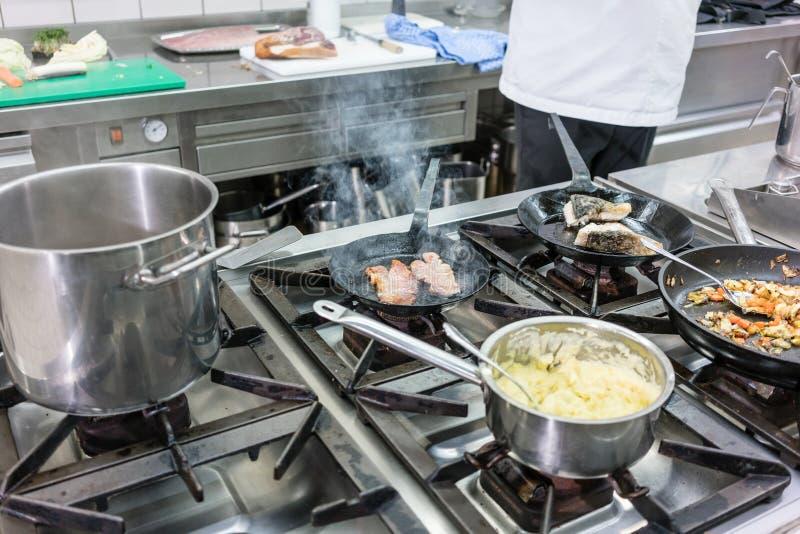 Potenciômetros e bandejas no fogão na cozinha do restaurante, o funcionamento do cozinheiro chefe mim fotografia de stock