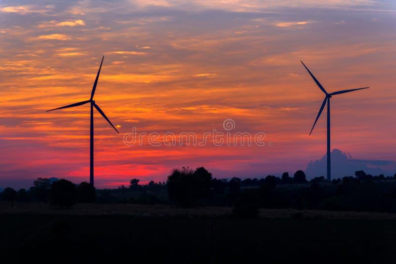Potere di Eco nell'azienda agricola del generatore eolico con il tramonto fotografia stock libera da diritti