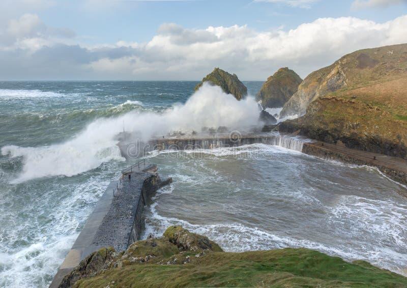 Potere di Wave sopra le pareti del porto alla baia del montante, Cornovaglia immagine stock