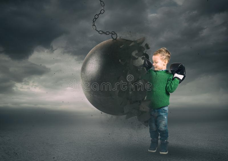 Potere e determinazione di un bambino contro una palla di distruzione immagini stock