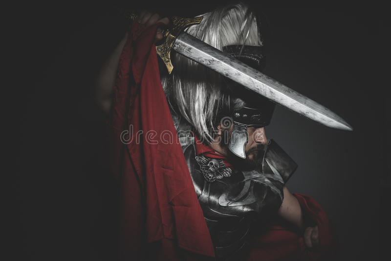 Potere, legionario romano pretorio e mantello, armatura e spada rossi fotografie stock