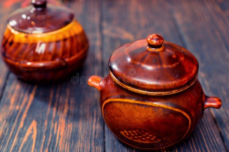 Potes de arcilla en un escritorio de madera imágenes de archivo libres de regalías