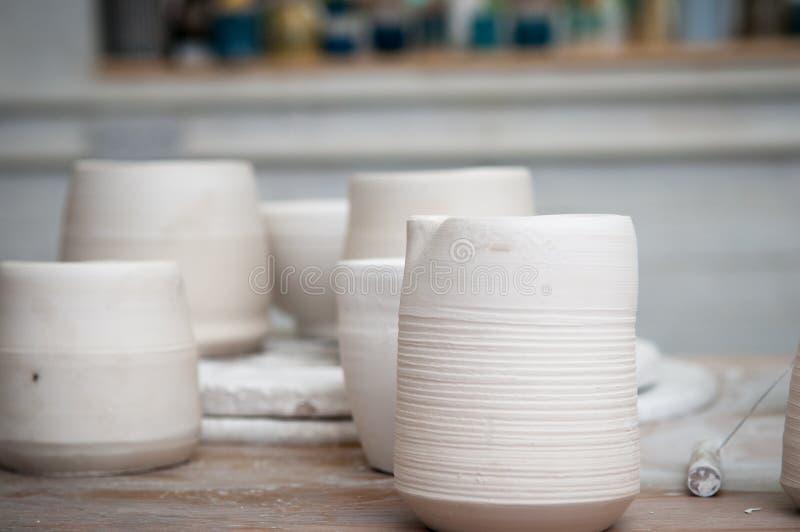 Potes de arcilla hechos a mano en un taller de la cerámica foto de archivo