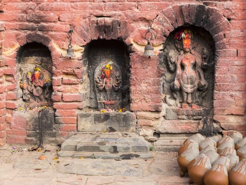Potes de arcilla que se secan al lado de tres lugares con viejas deidades hindúes talladas foto de archivo libre de regalías