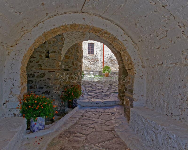 Potes griegos de la isla, de la puerta y de flores debajo de un arco del vintage imagen de archivo