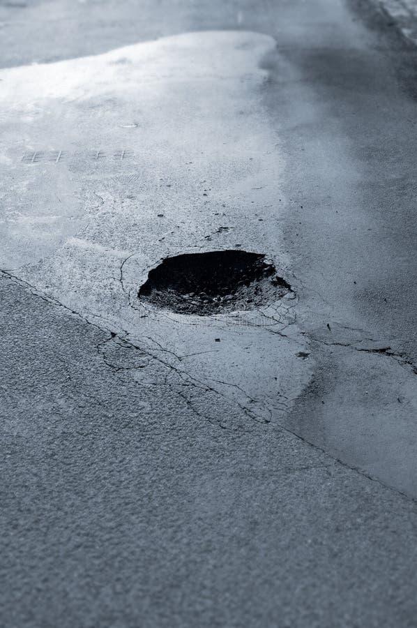 Pothole. Dangerous pothole on a road stock photo