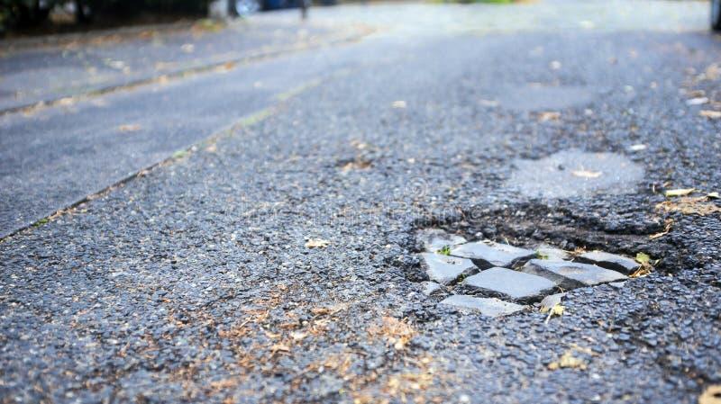 Pothole with old bricks on empty street stock image