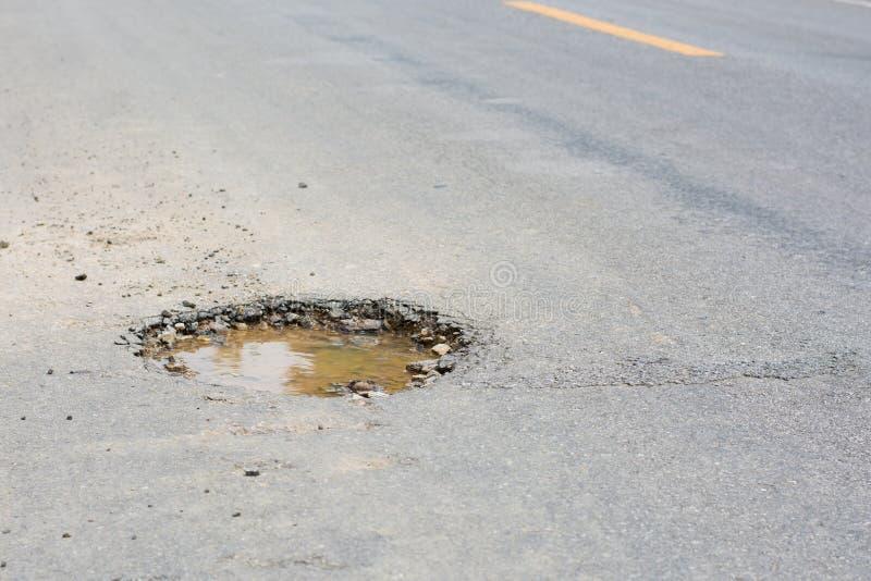 Pothole op de weg stock afbeeldingen