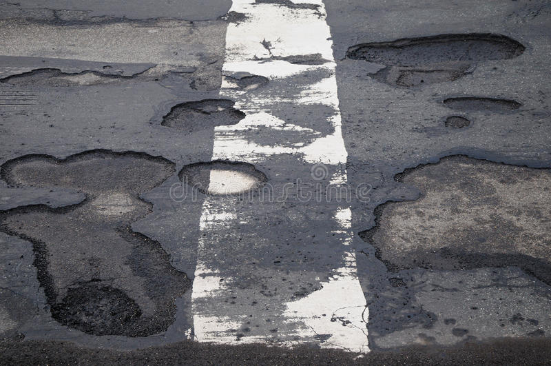 Potholes. Damaged road with potholes and a white dividing line stock photography