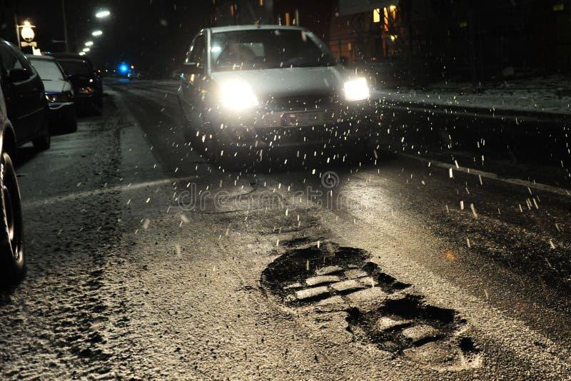 Potholes met auto bij nacht stock afbeelding