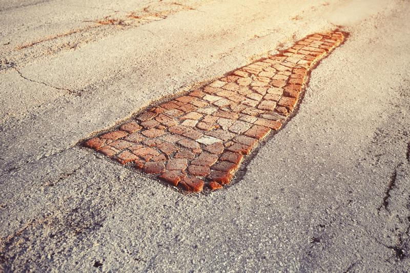 Potholes in the road sealed with old bricks. Creative way to repair when there is no money in the budget royalty free stock image
