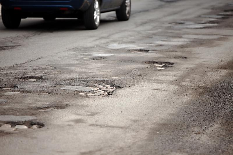 Potholes. Very bad quality road with potholes royalty free stock image