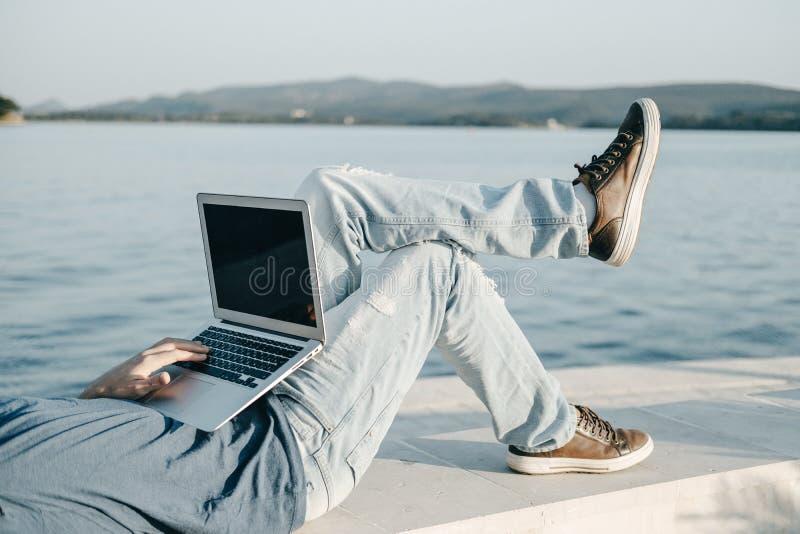 Poti la foto delle free lance del giovane che lavorano con il computer portatile che si siede la n immagine stock
