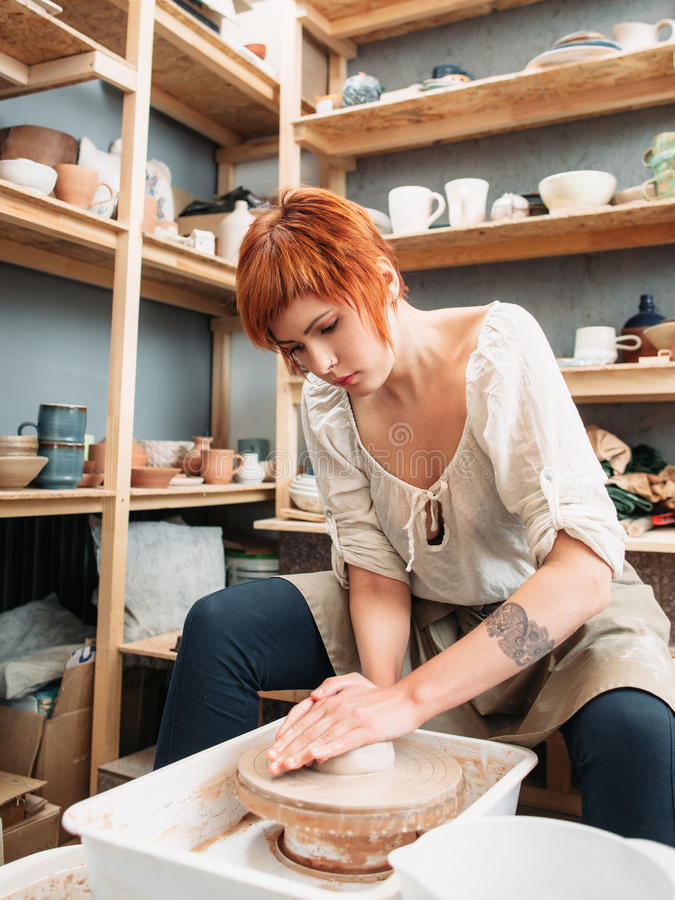 Potier féminin travaillant avec la roue de potiers photographie stock libre de droits